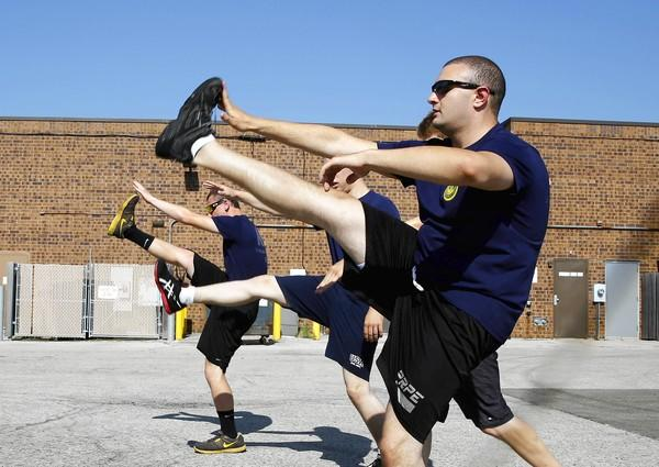 Herschel Gilbert, 20, at right, leads three other future sailors in their daily physical training regimen at the Armed Forces Recruiting Center in Crystal Lake.