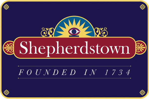 The new Shepherdstown sign was designed by area resident Bob Shelley. Things came together when Shelley saw the old Masonic Odd Fellows Eye logo above the small white library building in the middle of downtown. It became the sign's defining graphic element.