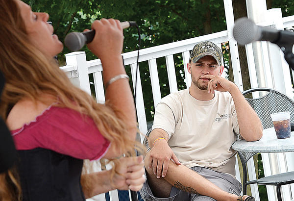 Daniel Martin listens to the sounds of Moondog Medicine Show singer Lana Spence Sunday at a fundraiser for Holly Place. The event was held at ThunderRoad Bar & Grille.