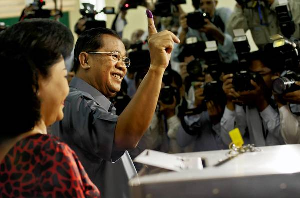 Cambodian Prime Minister Hun Sen shows his inked finger after voting in Kandal province.