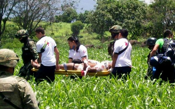 Rescuers carry a wounded victim of an attack on a Mexican navy convoy in Michoacan. Two people were killed, including a vice admiral.