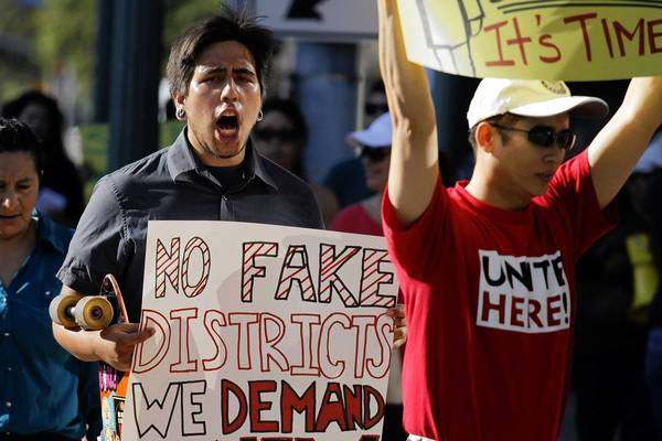 Anaheim resident Jesse Murillo, left, was among about 50 people protesting Anaheim's council election plan July 23. The council approved a requirement that members live in specific districts but did not change at-large voting.