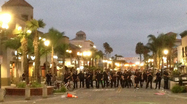 Police in riot gear converge on downtown Huntington Beach Sunday evening to break up an unruly crowd that had gathered following the U.S. Open of Surfing.