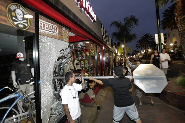 A man smashes a stop sign through the window of a bicycle shop at Main and Orange streets in Huntington Beach. Unrest occurred following the conclusion of the U.S. Open of Surfing. The unruly crowd also clashed with police.