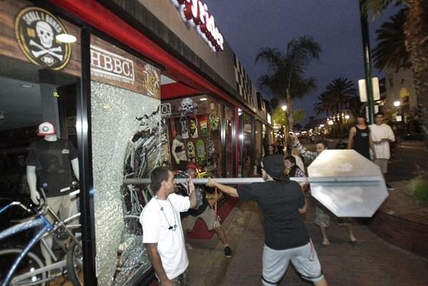 A rioter smashes a stop sign through the windows of Easyrider business on the corner of Main and Orange streets downtown Main Street in Huntington Beach following the US Open of Surfing contest finals. A few rioters looted a bike and other items from the store.
