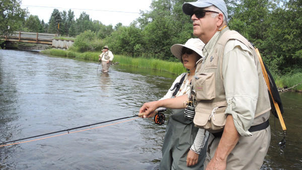 Volunteer guide Tony Alongi of Shelby Township helps Jin Huang of Troy cast to fish on the Au Sable in front of Gates Au Sable Lodge near Grayling. Upriver is volunteer guide Barry Coddens of Grayslake, Ill.