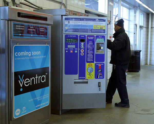 A CTA employee changes money cartridges on a transit card machine next to a Ventra fare system machine at the Western Blue Line station in March.