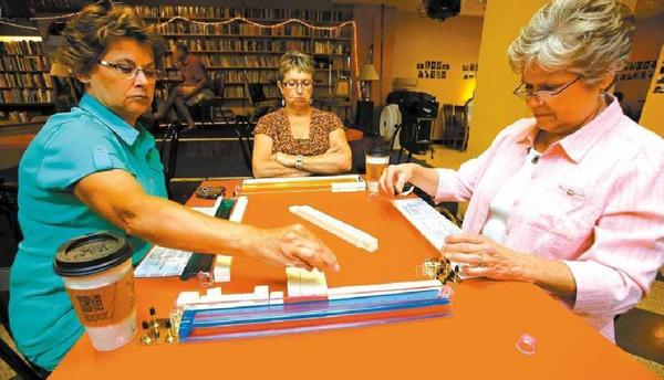 Ginger Westra, left, arranges tiles as Dee Sanderson, back center, and Lynn Sandvig, right, look over the tiles they drew as they begin a game of mahjong on Wednesday at the Red Rooster Coffee House. American News Photo by John Davis