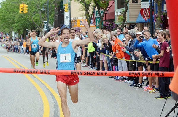 Daniel Clark of Jackson celebrates as he crosses the finish line to win his second straight Ryan Shay Mile mens title Saturday in Charlevoix. Clark finished in 3 minutes, 56.85 seconds.