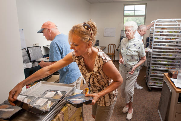 Rebecca Yager, of Enfield, and other volunteers for Enfield's Meals On Wheels service sort meals for delivery.