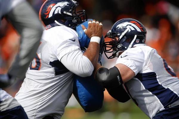Denver Broncos defensive tackle Romney Fuga (left) and center Dan Koppen square off during practice at the Broncos training facility last week.