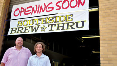 Owners of the new Southside Brew-Thru, Todd Holbay and Mike Pilot, stand at the exit of the drive-thru beer distributor.