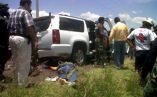 Army and Red Cross personnel stand next to the body of a victim, after a vehicle carrying a Mexican navy vice admiral was attacked by gunmen in Michoacan state.