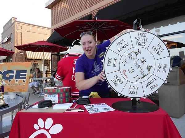 Melissa Ferriter, a volunteer for The Bridge Teen Center, shows off the Chick-fil-A prize wheel during last year's car show and fundraiser for the center. For a $1 donation to the center, guests can spin the wheel and win a Chick-fil-A food item or prize. This year's event is on Aug. 7, from 5 to 9 p.m., outside the restaurant, 16505 S. La Grange Road in Orland Park.