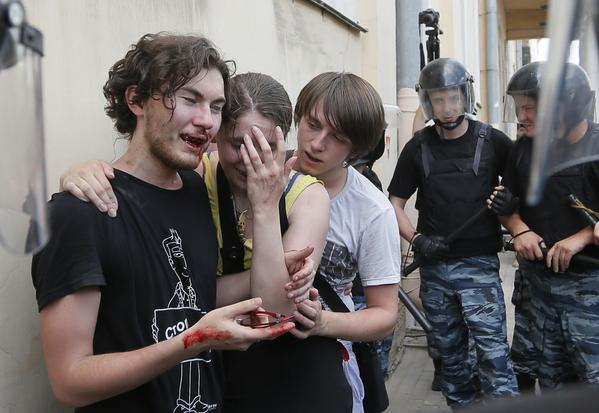 Riot police guard gay rights activists beaten by anti-gay protesters during a gay rights rally in St. Petersburg, Russia.