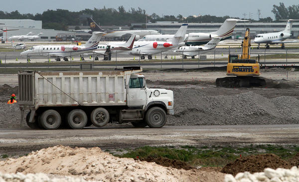 A dump truck transports a load of fill at the airport.