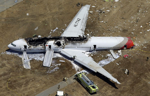 The wreckage of Asiana Airlines Flight 214 lies on the ground after it crashed at San Francisco International Airport on July 6. A couple has been charged in a luggage theft case in the resulting chaos at the airport.