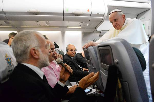 Pope Francis answers questions during a news conference aboard the papal flight to Rome from Brazil.