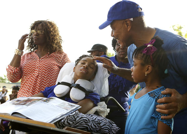 Danielle Sampson closes her eyes as her father Justin Fletcher touches her head at The Well of Hope church in Orlando on July 29, 2013. Also pictured is Danielle's mother Alma Fletcher, left, and niece Leila Fletcher, 7.