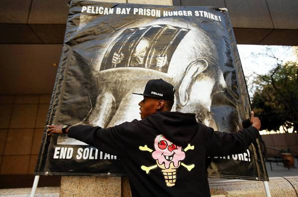 Inmate advocacy groups have called for an investigation into the death of hunger striker Billy Sell at the California state prison in Corcoran. Corrections officials said Sell had already resumed eating when he apparently killed himself in his cell. King County Chief Deputy Coroner Tom Edmonds said Monday that he had ruled Sell's death a suicide by strangulation but was awaiting toxicology results before issuing a report. Above, Slim Ballin, 19, of Los Angeles holds a sign in support of the group Stop Mass Incarceration Network during a rally in downtown Los Angeles on Monday in support of Sell.