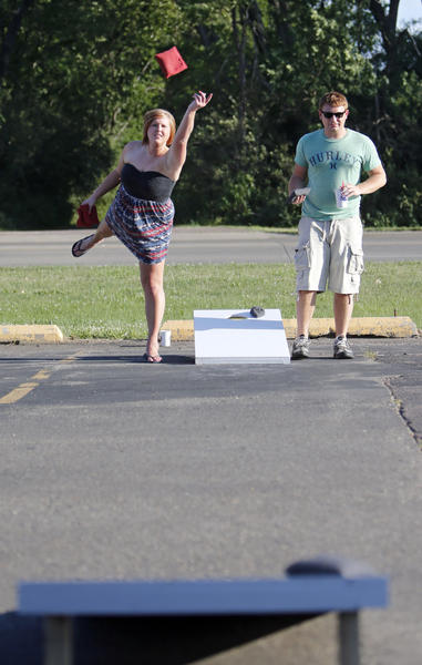 Cortney Gatzke, left, lets go of a bean bag as she and Carson Hardie, right, compete in a bean bag toss game Thursday in the parking lot of the Aberdeen Ramada Inn.