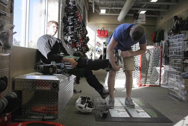 Jack Dolby, left, gets his skates sharpened at Perani's Hockey World. The chain opened its first Chicago-area location at Northbrook's North Shore Ice Arena in July.
