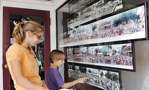 Kerri Barnes and her son Nicholas, of Greencastle, Pa., look over a display of past Old Home Week panoramic group photos displayed at the 2010 Old Home Week Headquarters.