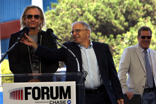 Joe Walsh of The Eagles, left, gets some help with his mike by Irving Azoff, of Azoff Music Management, as Glenn Frey, of The Eagles laughs during a press conference formally unveiling Madison Square Garden's plan to revitalize the Forum in Inglewood.