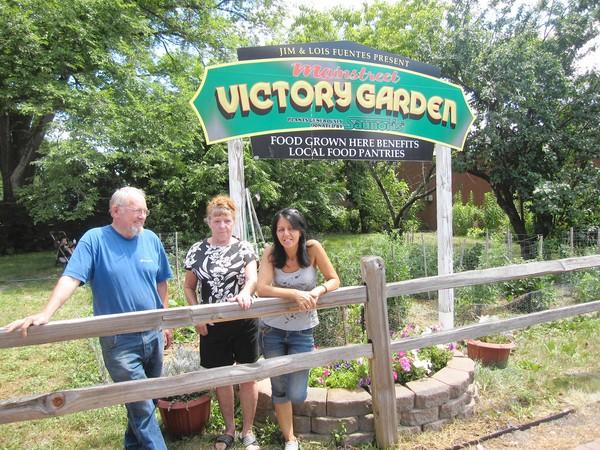 Ed and Pat Siemsen, left, stand in front of Tinley Park's Victory Garden with coordinator Julie Dekker, right. The garden on Oak Park Avenue is celebrating five years of feeding people in need.
