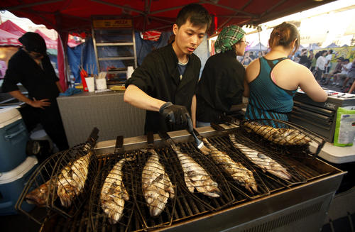 Lewis Chen grills whole fish over open coals, basted with olive oil and butter and doused with red pepper flakes, at Honey's BBQ at the Richmond Night Market. The market features small smokey food booths with everything you could imagine.