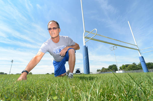 Boonsboro High School's Head Football Coach Clayton Anders poses on Warrior Field. The possibility of installing artificial turf on the field is being discussed.