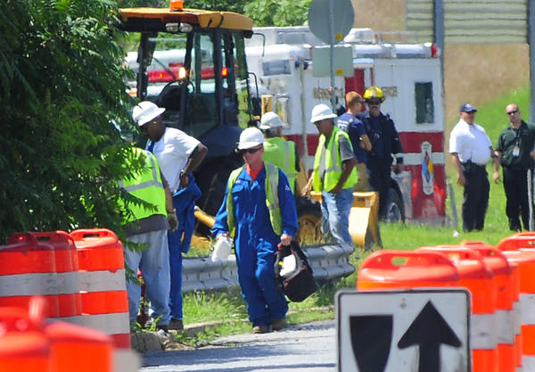 Columbia Gas workers, in blue jumpsuits, work Tuesday to turn off gas leaking from an underground pipe at Md. 63 near the Interstate 70 overpass.
