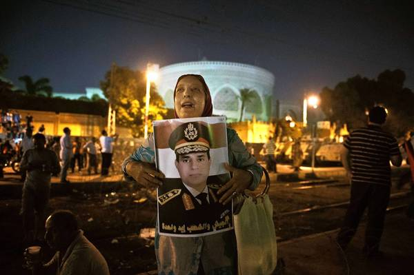 A woman holds a portrait of Egypt Defense minister Abdelfatah al-Seesi outside the presidential palace in Cairo on July 19.