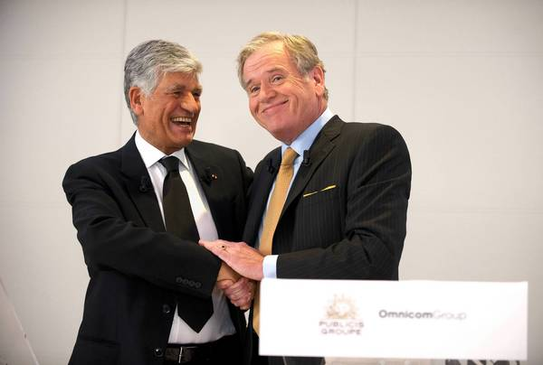 Maurice Levy, CEO of Publicis Groupe, left, and John Wren, CEO of Omnicom Group, shake hands after signing the merger deal during a news conference Sunday at Publicis headquarters in Paris.