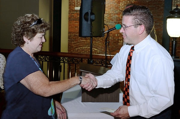 Kathy Bartels, deputy chief of Rehab 255 of Washington County, shakes hands with Bonanza Extravaganza treasurer Glenn Fuscsick, who presented her with a check for $3,500 on Tuesday evening.