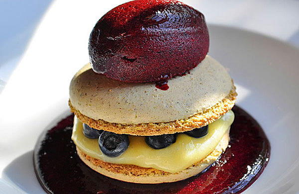 Pistachio macaron filled with lemon curd and local fresh blueberries, then garnished with blueberry puree and blueberry sorbet.