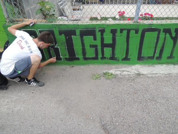 Noel Godinez, a 16-year-old Back of the Yards resident, outlines letters on the Brighton Kelly Baseball League mural.