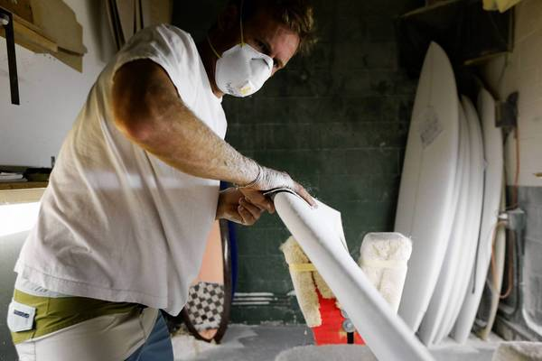 The Commerce Department reported Wednesday that the economy expanded at a 1.7% annual rate in the second quarter, exceeding analyst expectations of about 1% growth. Above, James Wheatley works on a Becker Surfboard in Hermosa Beach.