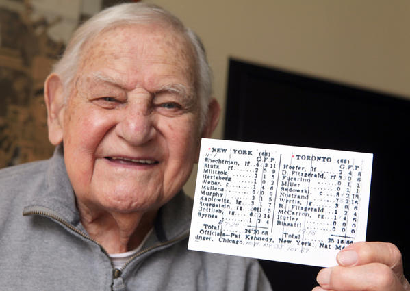 Holding a box score from the first NBA game in Toronto, Ossie Schectman, 93 of New City, N.Y. smiles while talking about scoring the first basket when he was a member of the New York Knickerbockers.