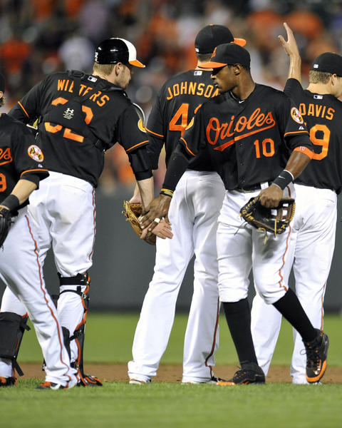 Baltimore Orioles teammates Matt Wieters (32) and Adam Jones (10) celebrate after defeating the Red Sox at Oriole Park.