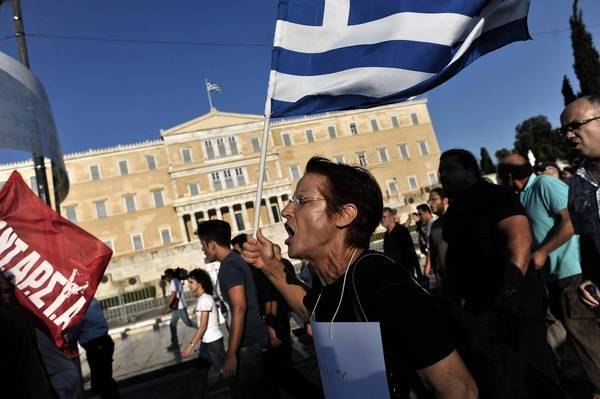 Protesters shout slogans against the visit of the German finance minister as they demonstrate in front of the Parliament building in central Athens in mid-July.