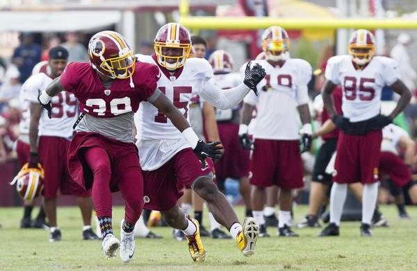 Josh Morgan, right, attempts to get around rookie David Amerson during a drill at Redskins training camp Tuesday in Richmond.