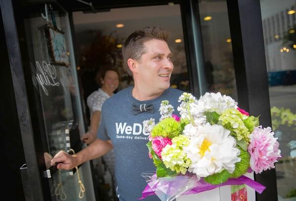 Byron Zook, a courier for the new Chicago startup WeDeliver, picks up flowers from Lincoln Park florist Dilly Lily in Chicago. WeDeliver provides same-day delivery for local merchants through its network of couriers.