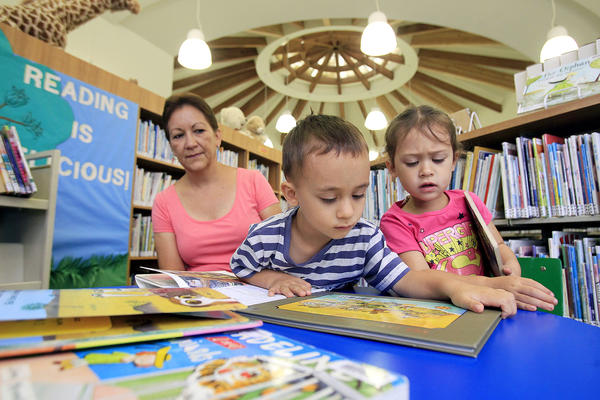 Catalina Ospina, left, watches as three-year-old twins Jeremiah, center, and Melia Kearns look through children's animal books during the reopening of Donald Dungan Library in Costa Mesa on Wednesday.