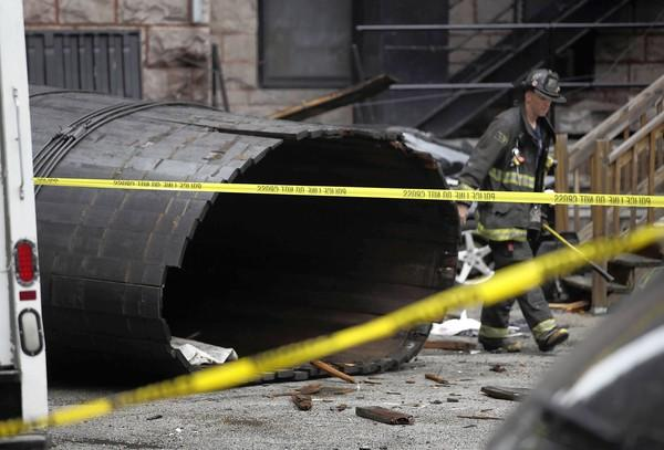 Chicago authorities investigate a fallen water tower in the 2800 block of North Pine Grove Avenue in the Lakeview neighborhood Wednesday. It fell eight stories and injured three people.