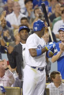 Kobe Bryant, left, gestures as Yasiel Puig looks on during the fourth inning of the Dodgers' matchup with the New York Yankees at Dodger Stadium on Wednesday.