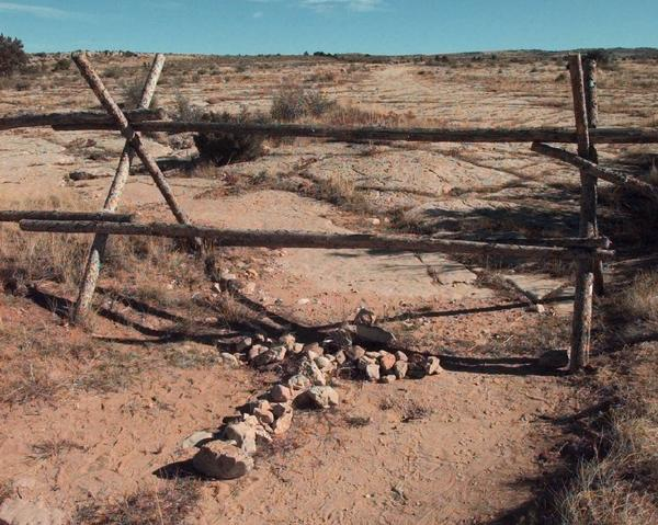 A cross made of stones rests below the fence in Laramie, Wyo., where University of Wyoming student Matthew Shepard was beaten to death.