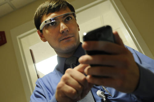 Chris Madison, of Hartford Hospital, looks at an image on Google Glass as he simultaneously uses his phone during a mock medical emergency in the Center for Education Simulation and Innovation, CESI. Since Google did not give the glasses to institutions or business, and each Glass is given to an individual, Madison is the individual at Hartford Hospital who actually received the highly sought after wearable technology and is working on custom applications integrating it with their simulation system. Madison said he wore them two weeks straight, and noticed that he began to rely on them after he no longer wore them for a while.