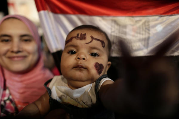 "Qurbah, a 6-month-old girl with ""Morsi"" (in Arabic) painted on her face, attends a demonstration with her mother outside the Rabaa al Adawiya mosque in Cairo."