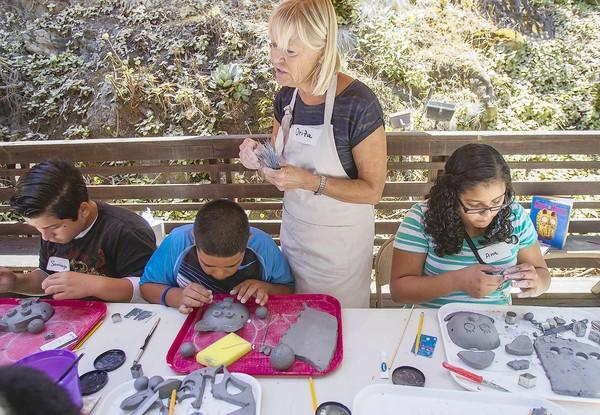Ora Sterling, center, teaches a a mask-making class using ceramics to Santiago Torres, 13, left, Romario Alvarez, 11, and Ana Frutos, 12, right, at the Sawdust Art Festival on Tuesday. The students were with Project Access within the Warwick Center, a housing community in Santa Ana.